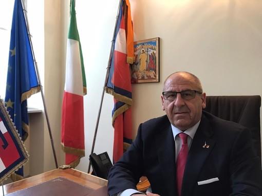 Uomo in giacca e cravatta seduto alla scrivania