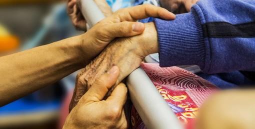 mano di anziano tenuto nel letto di una rsa