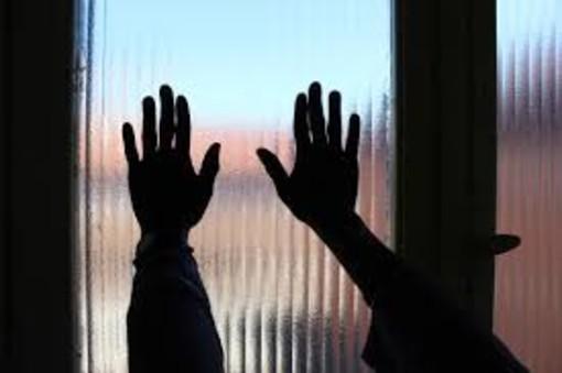 Mani contro il vetro di una finestra